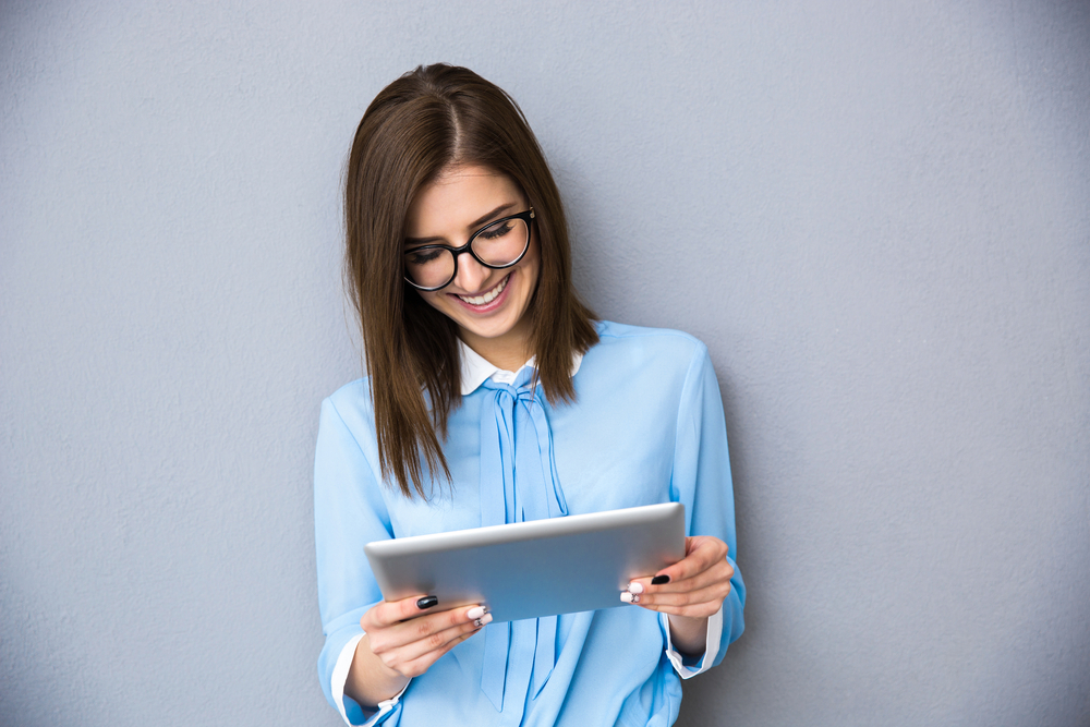 Happy businesswoman standing with table computer over gray background. Wearing in blue shirt and glasses.-1
